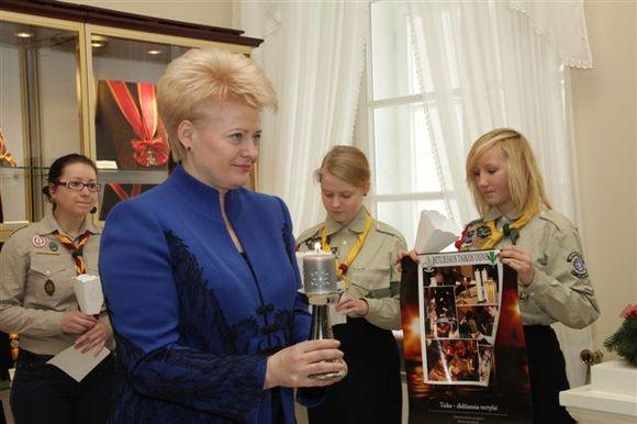 Prezidentė priima skautų atneštą žvakelę.