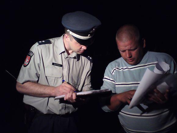 Sauliaus Chadasevičiaus/15min.lt nuotr./Badautojų stovyklos patikrinti naktį atvykęs pareigūnas papraaė dokumentų ir užsiraaė kai kuriuos duomenis.