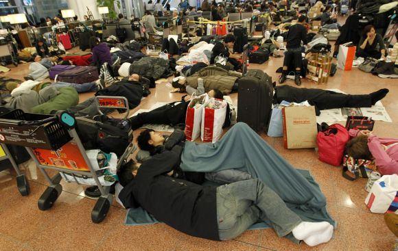 Reuters/Scanpix nuotr./Daugybė žmonių tiesiog apsigyveno Tokijo oro uoste, tikėdamiesi sulaukti galimybės iavykti.