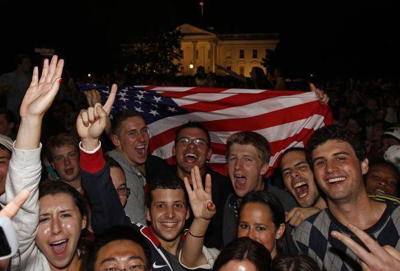 Reuters/Scanpix nuotr./Po Baracko Obamos kalbos per televiziją apie nukautą Osamą bin Ladeną prie Baltųjų rūmų Vaaingtone ėmė rinktis triumfuojantys amerikiečiai.