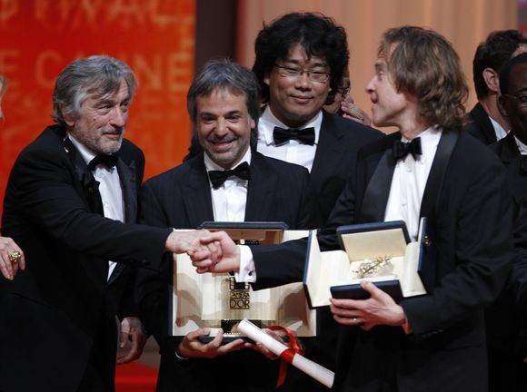 Reuters/Scanpix nuotr./Žiuri pirmininkas Robertas de Niro sveikina geriausio filmo prodiuserį
