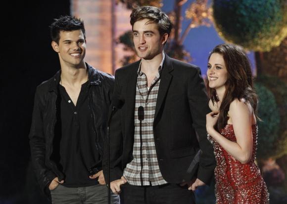 2011-ųjų MTV kino apdovanojimuose: (iš kairės) Tayloras Lautneris, Robertas Pattinsonas ir Kristen Stewart.