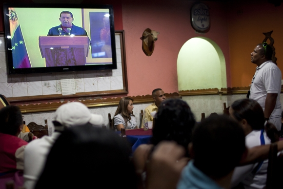 Vieno Venesuelos sostinės Karakaso baro lankytojai stebi Hugo Chavezo kalbą per televiziją.