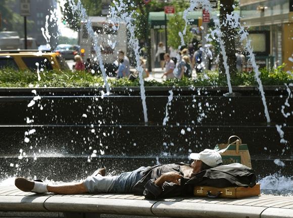 Vyras guli šalia fontano.