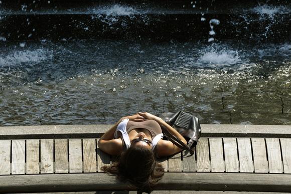 Mergina aušinasi prie fontano.