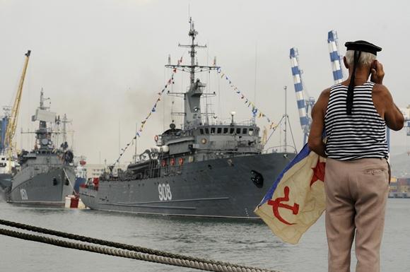 Vyras žiūri Rusijos karinių laivų paradą