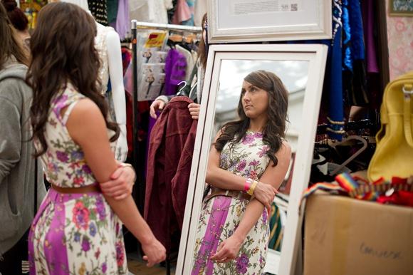 Retro drabužiais apsirengusi moteris prie veidrodžio