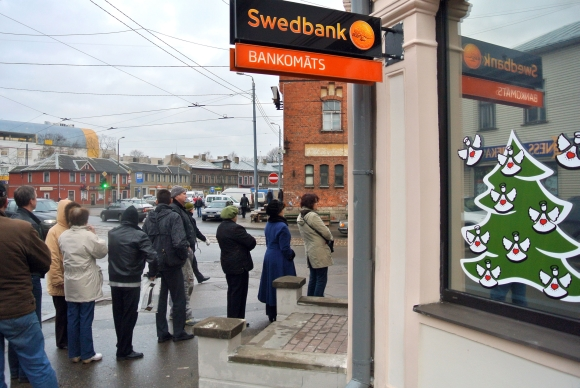 """Žmonės stoja į ilgą eilę Rygoje, kad atsiimtų savo pinigus iš """"Swedbank"""" bankomato."""