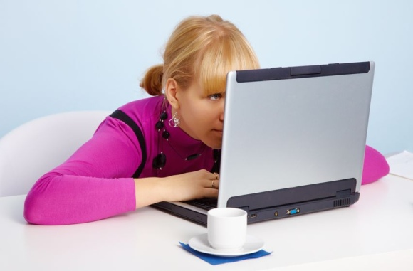 Moteris akylai žiūri į kompiuterio ekraną