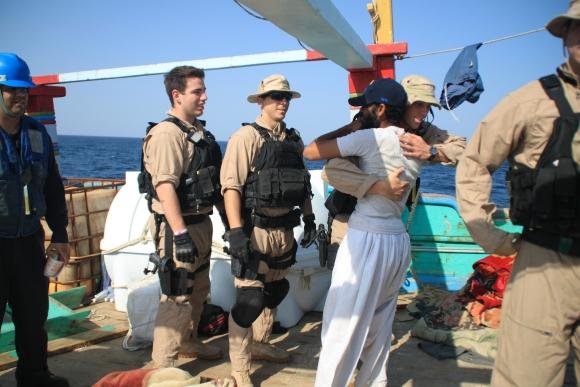 """JAV jūreivis iš laivo """"Kidd"""" sveikinasi su iraniečiu, išgelbėtu iš piratų nelaisvės."""