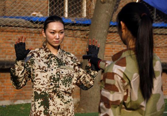 Scanpix nuotr./Kinijoje ruoaiamos moterys asmens sargybinės