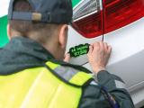"""Juliaus Kalinsko/""""15 minučių"""" nuotr./Kelių policininkas ant automobilio klijuoja lipduką """"Aš neimu kyšio"""""""