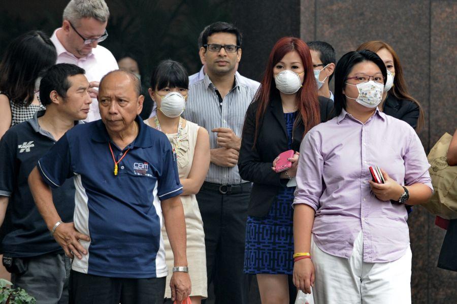 Singapūro žmonės nuo teršalų saugosi apsaugiinėmis kaukėmis.