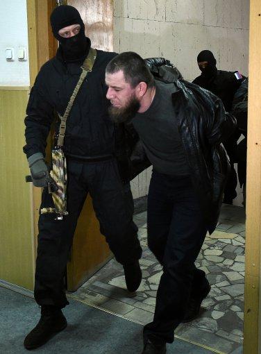 """AFP/""""Scanpix"""" nuotr./Į teismą atvedamas įtariamasis"""