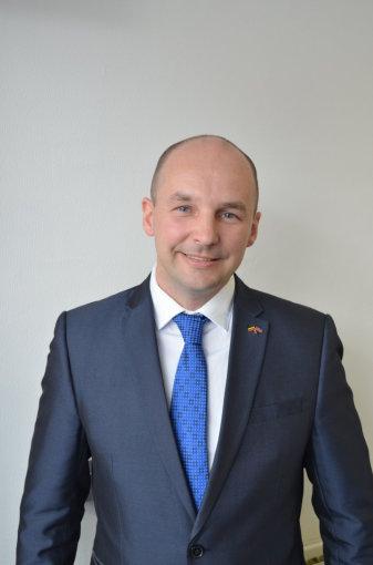 Eduardas Gaulia su Lietuvos ambasadorės Jungtinėje Karalystėje padovanotu kaklaraiščiu bei Lietuvos ir JK vėliavėlių ženkliuku