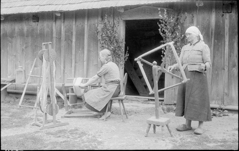 Moteris dešinėje iš verpimo ratelio špūlės veja siūlus ant lenktuvo, moteris kairėje nuo lenktuvo veja siūlus ant krijelio
