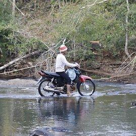 Medkirtys, besikeliantis per upę motoroleriu