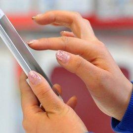 """AFP/""""Scanpix"""" nuotr./Moteris naudojasi išmaniuoju telefonu"""