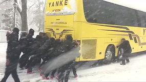 Moterų krepšinio komandai teko stumti sniege įstrigusį autobusą