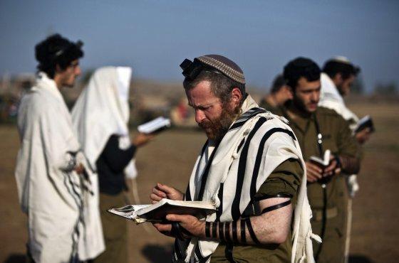 """""""Reuters""""/""""Scanpix"""" nuotr./Izraelio kariai meldžaisi netoli sienos su Gazos Ruožu."""
