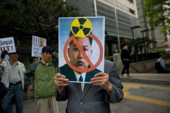 """AFP/""""Scanpix"""" nuotr./Protestuotojas Seule laiko plakatą su Šiaurės Korėjos lyderio Kim Jong Uno atvaizdu"""