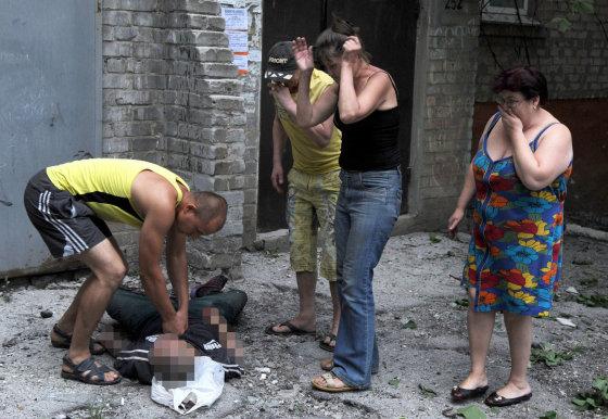 """AFP/""""Scanpix"""" nuotr./Vietos gyventojai prie pašauto vyro Slovjanske"""