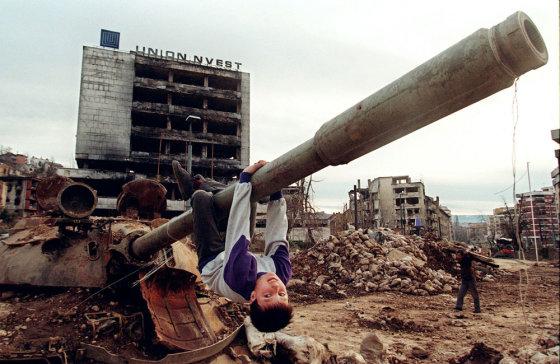 """AFP/""""Scanpix"""" nuotr./Sarajeve vaikas žaidžia ant palikto tanko vamzdžio"""