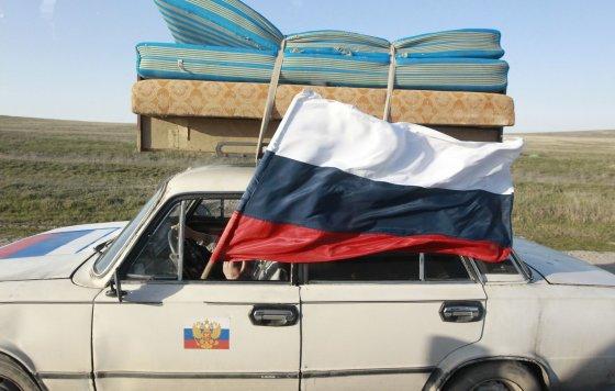"""""""Reuters""""/""""Scanpix"""" nuotr./Per automobilio langą iškišta Rusijos vėliava"""