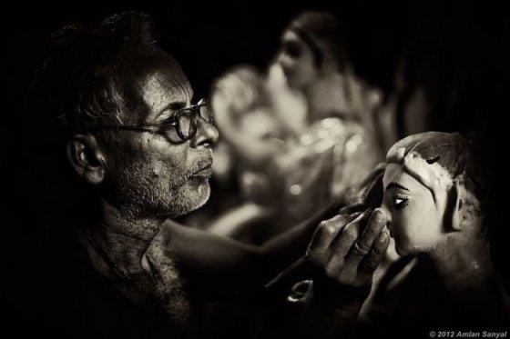 Menininkas piešia veidą vienai iš deivių skulptūrų