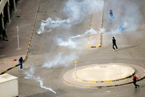 """""""Reuters""""/""""Scanpix"""" nuotr./Nuo ašarinių dujų bėgantys protestuotojai."""