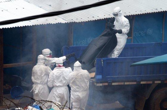 """AFP/""""Scanpix"""" nuotr./Į sunkvežimį keliamas nuo Ebolos viruso mirusio žmogaus kūnas"""