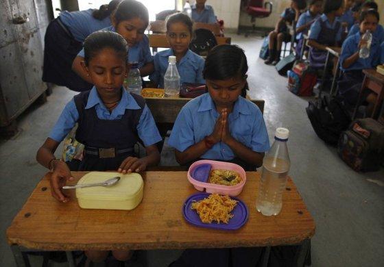 """""""Reuters""""/""""Scanpix"""" nuotr./Indijos mokykloje mokiniai meldžiasi prieš valgydami pietus."""
