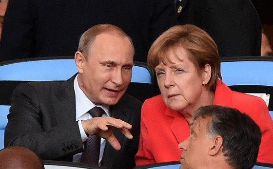 """AFP/""""Scanpix"""" nuotr./Rusijose prezidentas Vladimiras Putinas ir Vokietijos kanclerė Angela Merkel 2014 metų Pasaulio futbolo čempionato finale"""