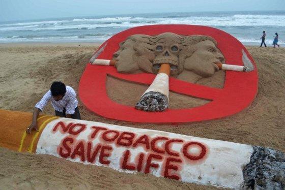 """AFP/""""Scanpix"""" nuotr./Smėlio skulptoriaus darbas skirtas paminėti dienai be tabako"""
