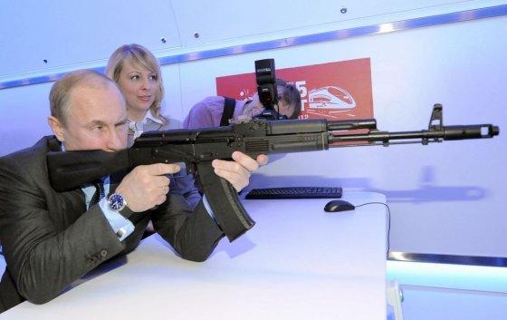 """AFP/""""Scanpix"""" nuotr./Vladimiras Putinas ginklų parodoje išbandė Kalašnikovo kopiją."""
