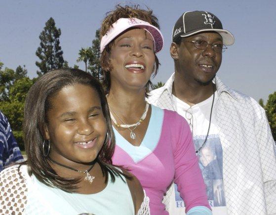 """""""Reuters""""/""""Scanpix"""" nuotr./Whitney Houston ir Bobby Brownas su dukra Bobbi Kristina Brown (2004 m.)"""