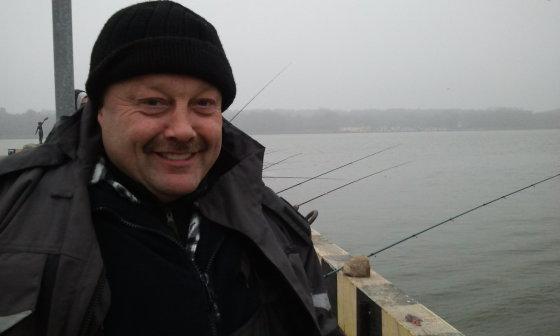 L. Sėlenienės nuotr./Žvejys Saulius svarsto, kad tamsoje stintos geriau kimba, kad   Kruizinių laivų terminale žada likti ir nakčiai.