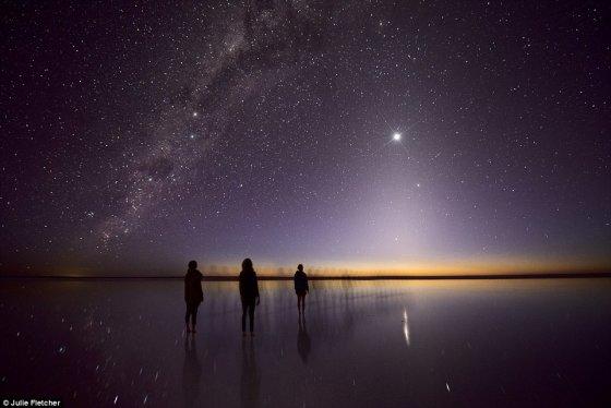 Jule Fletcher nuotr./Naktinio skliauto žvaigždės virš horizonto rikiuojasi į piramidę, kurios viršūnėje – skaisčiai žėrintis Veneros deimantas. Kerintį vaizdą įbridusios į Eirio ežero vandenis netoli Kati Thanda stebi trys moterys