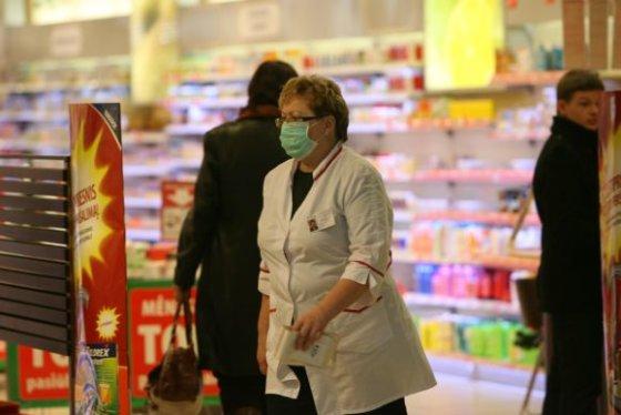 scanpix.lt nuotr./Vaistinės darbuotoja nuo siautėjančio gripo saugosi dėvėdama kaukę.