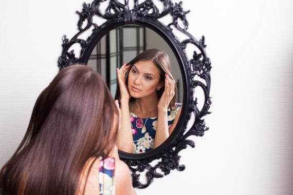 Shutterstock nuotr./Moteris žiūri į veidrodį