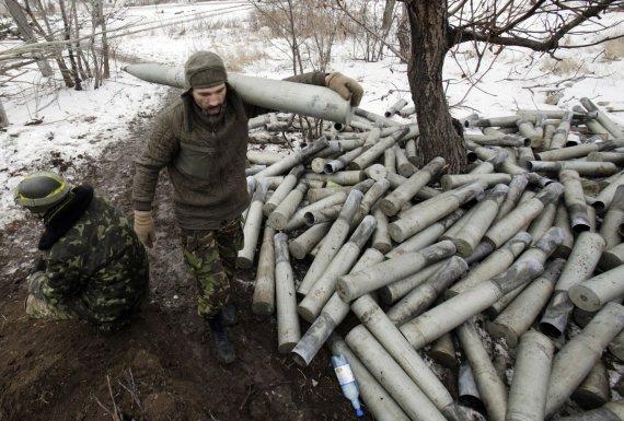 """AFP/""""Scanpix"""" nuotr./Ukrainos karys eina šalia krūvos panaudotų artilerijos sviedinių tūtų."""