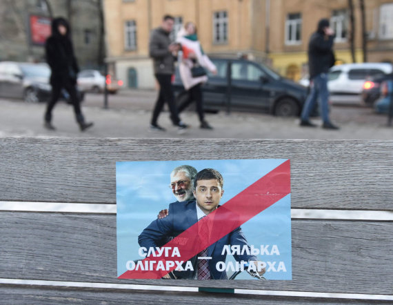 """AFP/""""Scanpix"""" nuotr./Plakatas su užrašu """"Oligarcho tarnas"""". Ant jo – Ihoris Kolomoiskis ir Volodymyras Zelenskis"""