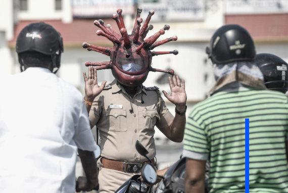 """AFP/""""Scanpix"""" nuotr./Virusu persirengęs pareigūnas Indijoje išradingai kovoja su COVID-19 užkrato plitimu"""
