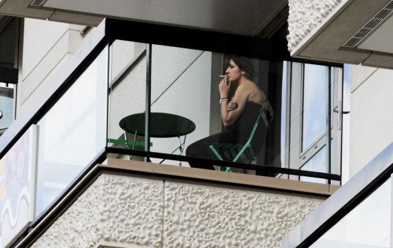 """""""Reuters""""/""""Scanpix"""" nuotr./Rūkanti moteris balkone"""