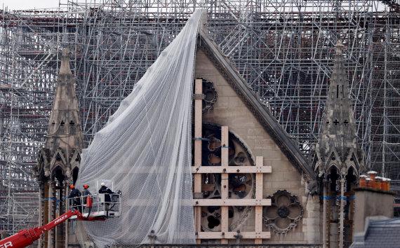 """""""Reuters""""/""""Scanpix"""" nuotr./Paryžiuje darbininkai pradeda šalinti gaisro apgadintus pastolius Dievo Motinos katedroje"""