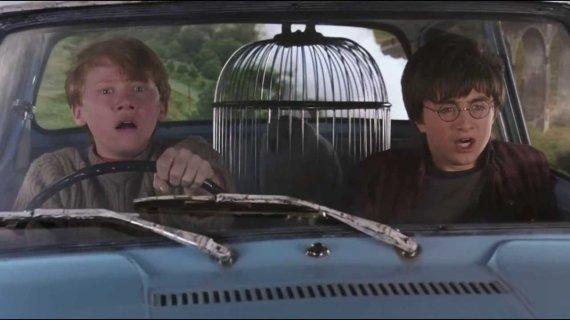 """Kadras iš filmo """"Haris Poteris ir paslapčių kambarys""""/ scena, kai Haris ir Ronis į Hogvartsą skrenda magišku Artūro Vizlio automobiliu"""