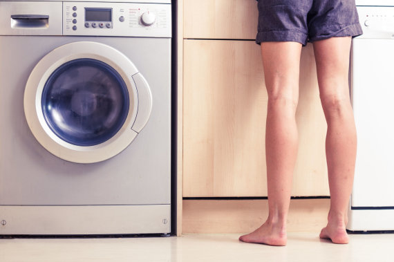 Vida Press nuotr./Moteris prie skalbimo mašinos