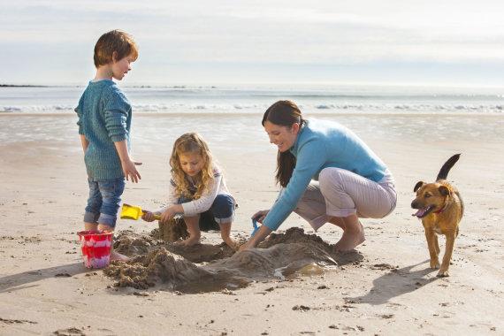 123RF.com nuotr./Šeima su augintiniu paplūdimyje