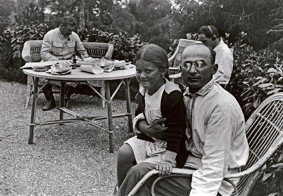 Wikipedia.org nuotr./Josifo Stalino dukra Svetlana vaikystėje sėdi ant Lavrentijaus Berijos kelių. Fone prie stalo – J.Stalinas