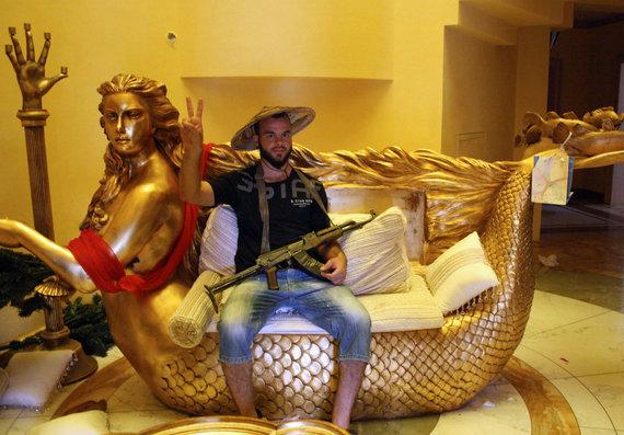 """AFP/""""Scanpix"""" nuotr./Sukilėlis ant auksinės undinėlės formos sofos (2011 m. rugpjūtis)"""